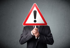 Businessman holding an exclamation road sign Stock Photos