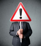 Businessman holding an exclamation road sign Stock Photography
