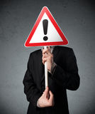 Businessman holding an exclamation road sign Royalty Free Stock Images