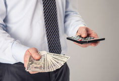 Businessman holding fan of dollar banknotes and calculator Royalty Free Stock Photography