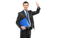 Businessman holding a fascicule and giving thumb Stock Images