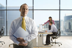 Businessman holding file with co-workers working in background Stock Image