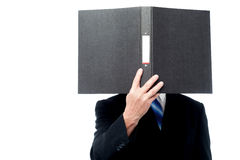 Businessman holding file pad and cover his face Stock Photography
