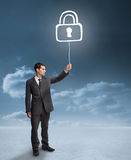 Businessman holding a floating padlock Royalty Free Stock Photo
