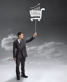 Businessman holding a floating shopping cart Royalty Free Stock Photos