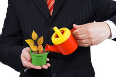 Businessman holding a flower pot and watering can. Isolated on white background Stock Image