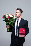 Businessman holding flowers and gift box Royalty Free Stock Photo