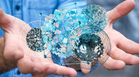 Businessman holding flying abstract sphere with shiny cube 3D re Stock Images