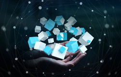 Businessman holding flying blue shiny cube 3D rendering. Businessman on blurred background holding flying blue shiny cube 3D rendering Stock Photos