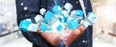 Businessman holding flying blue shiny cube 3D rendering. Businessman on blurred background holding flying blue shiny cube 3D rendering Royalty Free Stock Photography