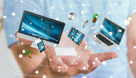 Businessman holding flying desk laptop phone and tablet in his h. Businessman on blurred background holding flying desk laptop phone and tablet in his hand 3D Royalty Free Stock Photography