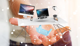 Businessman holding flying desk laptop phone and tablet in his h. Businessman on blurred background holding flying desk laptop phone and tablet in his hand 3D Royalty Free Stock Images