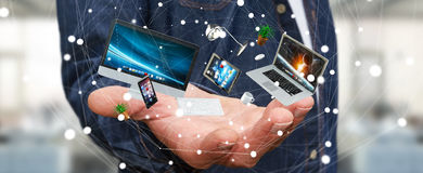 Businessman holding flying desk laptop phone and tablet in his h. Businessman on blurred background holding flying desk laptop phone and tablet in his hand 3D Royalty Free Stock Image