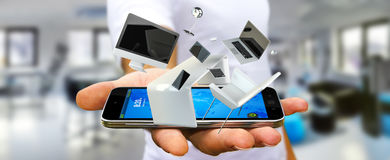 Businessman holding flying desk laptop phone and tablet in his h. Businessman on blurred background holding flying desk laptop phone and tablet in his hand 3D Stock Photography