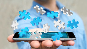 Businessman holding flying puzzle pieces '3D rendering'. Businessman holding flying puzzle pieces on his mobile phone '3D rendering Stock Photo