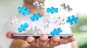 Businessman holding flying puzzle pieces '3D rendering'. Businessman holding flying puzzle pieces on his mobile phone '3D rendering Royalty Free Stock Photography