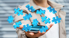 Businessman holding flying puzzle pieces '3D rendering'. Businessman holding flying puzzle pieces on his mobile phone '3D rendering Royalty Free Stock Photos