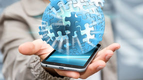 Businessman holding flying puzzle sphere '3D rendering'. Businessman holding flying puzzle sphere on mobile phone '3D rendering Stock Photography