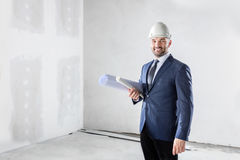Businessman holding folded documents at the construction site. Royalty Free Stock Photography