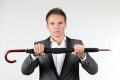 Businessman holding a folded umbrella Stock Images