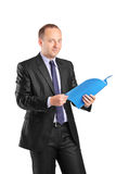 Businessman holding a folder and looking at camera Stock Photography