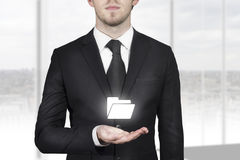 Businessman holding folder symbol in open hand Stock Photography