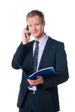 Businessman holding folder and talking on phone Stock Image