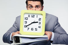Businessman holding folders and clock Stock Photography