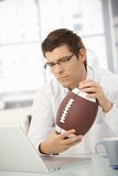 Businessman holding football Stock Image