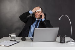 Businessman holding forehead in office. Royalty Free Stock Photos