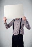 Businessman holding in front of his head a paper with copy space Royalty Free Stock Image