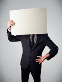 Businessman holding in front of his head a paper with copy space Stock Images