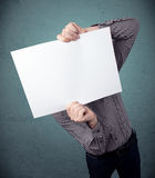 Businessman holding in front of his head a paper with copy space Royalty Free Stock Photography