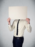 Businessman holding in front of his head a paper with copy space. Businessman standing and holding in front of his head a white paper with copy space Stock Image