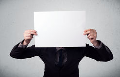 Businessman holding in front of his head a paper with copy space Stock Photos