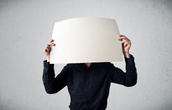 Businessman holding in front of his head a paper with copy space Royalty Free Stock Photos