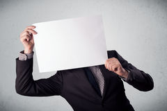 Businessman holding in front of his head a paper with copy space Stock Photography