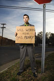 Businessman Holding Gas Money Sign. Young businessman stands on a street corner holding a sign that reads 'will work for gas money'. Vertical shot Stock Photo