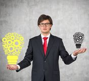 Businessman holding gears. In form lightbulb Royalty Free Stock Photo