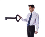 Businessman holding a giant key Stock Photo
