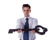 Businessman holding a giant key Stock Photography