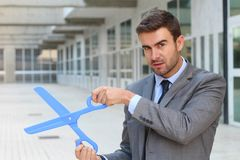Businessman holding a giant pair of scissors Stock Image