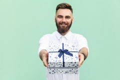 Businessman holding gift box and looking at camera and toothy smile. On light green background. Studio shot Stock Photos
