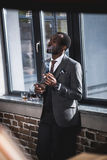Businessman holding glass with whiskey and smoking cigar indoors. Confident businessman holding glass with whiskey and smoking cigar indoors Stock Photos