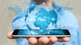 Businessman holding global network on planet earth 3D rendering. Businessman holding global network and data exchanges over his phone 3D rendering Royalty Free Stock Image