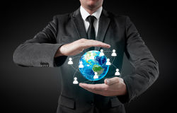 Businessman holding globe in his hands. The concept of personnel management around the world Stock Image