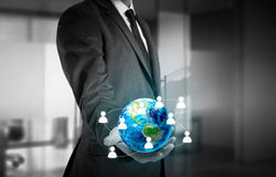 Businessman holding globe in his hands. The concept of personnel management around the world.  royalty free stock photography