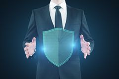 Safety and hack concept. Businessman holding glowing antivirus shield on blue background. Safety and hack concept. 3D Rendering royalty free illustration