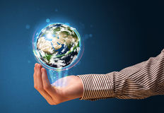 Businessman holding a glowing earth globe Stock Image
