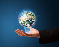 Businessman holding a glowing earth globe Stock Photos